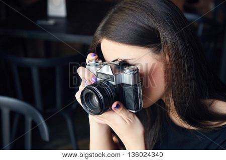 Young girl photographer with old analog film camera in cafe. Beautiful girl in black t-shirt is looking at viewfinder of camera and making photo. Girl is holding camera in her hands.
