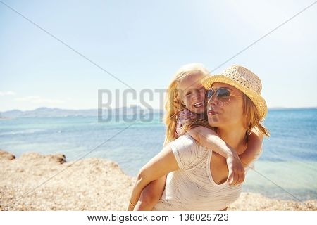 Laughing Little Girl With Her Mother At The Beach