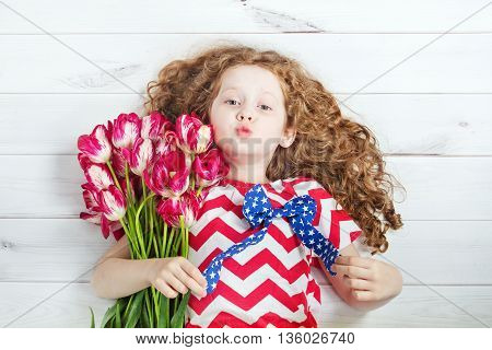 Cute little girl with red tulips and giving air kiss. Celebrating 4th july. Independence Day concept.