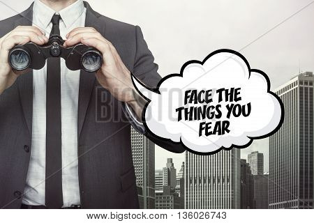 Face the things you fear text on speech bubble with businessman holding binoculars on city background