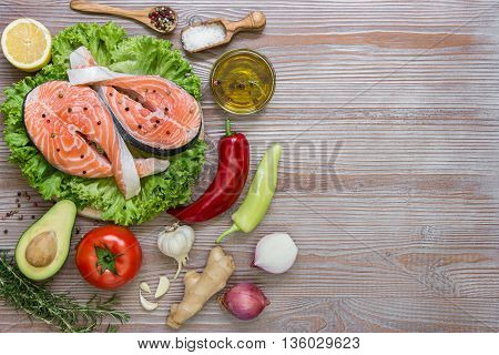 Left salmon fillets on lettuce near peppers tomato avocado onion rosemary lemon garlic spices salt olive oil right empty space on wood background. Salmon fillets and vegetables. Top view.