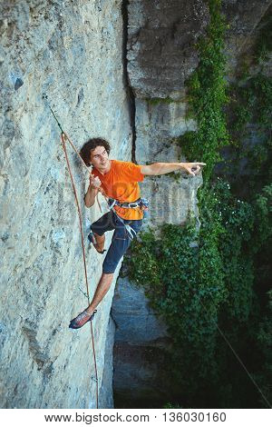 male rock climber. rock climber climbs on a rocky wall. man hanging on a rope and shows his hand towards