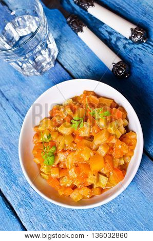 Vegetable stew with sauce on wooden background. Selective focus.