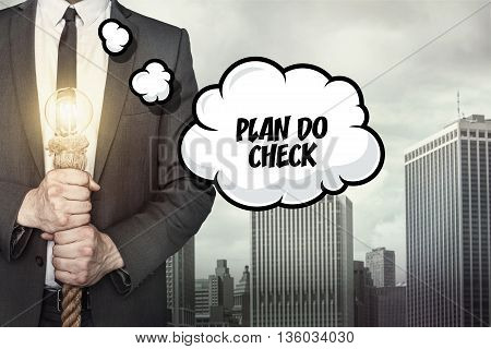 plan do check Text on speech bubble with businessman holding lamp on city background