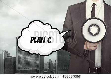 Plan c Text on speech bubble with businessman and megaphone on city background