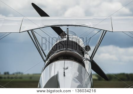 Old airplane - biplane at the airfield, back side view. Air concept of retro aviation. Wings, tail and fuselage of the airplane on airfield, rear view.
