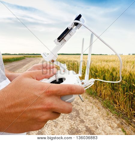 Demonstration of unmanned copter. Man controls quadrocopter flight. Flying the copter over a field of wheat. Remote control in a man's hands.