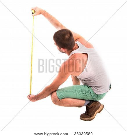 Man Measures The Wall With A Tape Measure