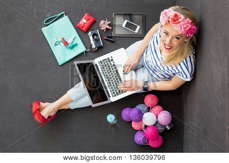 Fashion blogger with computer in her lap  looking up