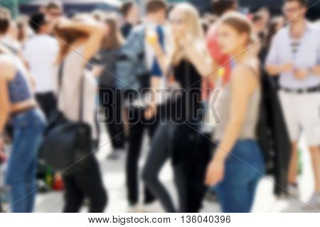 defocused crowd of young people mingling outside