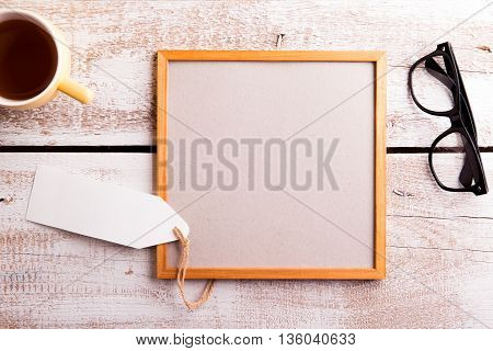 Empty Picture Frame, Eyeglasses And Cup Of Tea