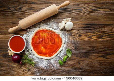 Pizza dough with ingredients, tomato sauce and wooden rolling-pin served on rustic wooden table. Aerial shot, copyspace for text