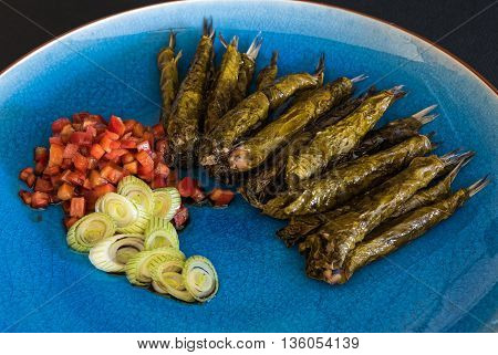 Anchovies in vine leaves, served with tomato salad and onions in blue plate