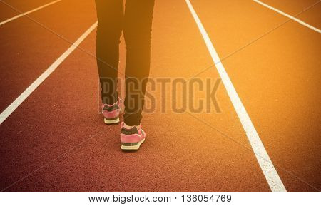 Woman walking on running track. Vintage tone.