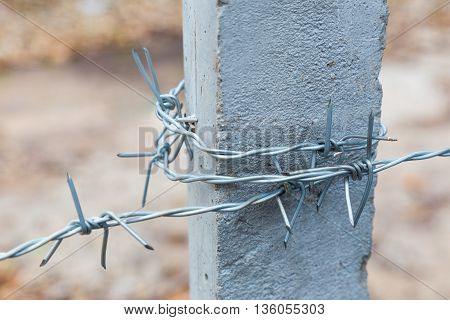 Barbwire wrapped around concrete post selective focus with blurred background