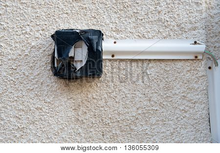 Dangerous and not safe broken door entry bell switch hanging on an external wall and covered with plastic tape to cover the bare electric wires.