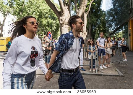 MILAN ITALY - JUNE 21: Fashionable couple posing outside Armani fashion show building during Milan Men's Fashion Week on JUNE 21 2016 in Milan.