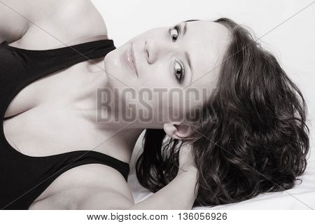 Sexy lazy girl in black body hugging a pillow on the bed. Young attractive woman lying lazing in bedroom at morning.