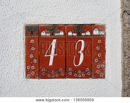 Tiled red house number 43 on the white stucco wall poster