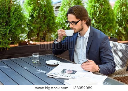 Young businessman enjoying coffee cup busy pensive phone sitting cafe newspaper