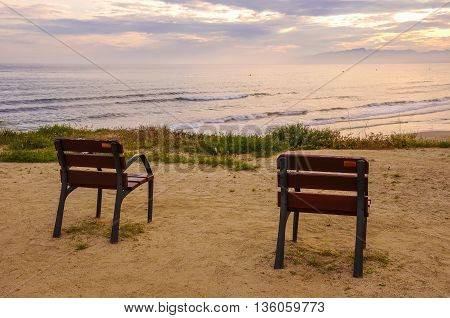 Two lonely chairs overlooking the Mediterranean sea at sunset. Horizontal.