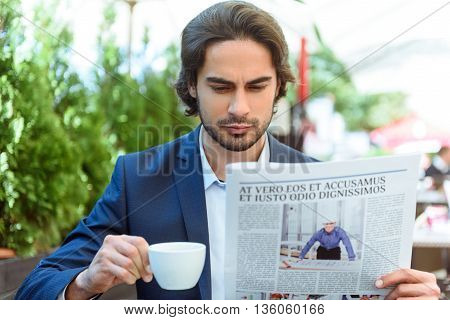 Serous man wants to know news. He is holding a paper and drinking coffee. Worker is sitting and resting in cafe