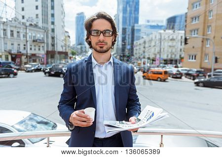 Cheerful young businessman is making break after work. He is holding a cup of coffee and paper. Man is standing and looking at camera with confidence