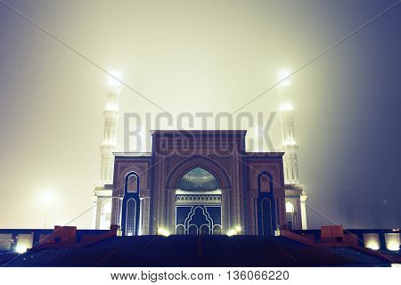 Mosque illumination at fogy weather at night.