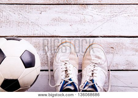 Soccer Ball, Cleats On White Wooden Floor, Studio Shot