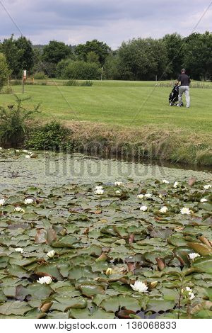 A golfer walking to the green on a par 3 with water in the foreground
