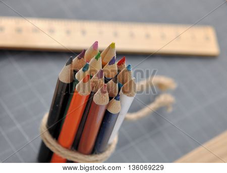 close on colored pencils with wooden rule on a slate