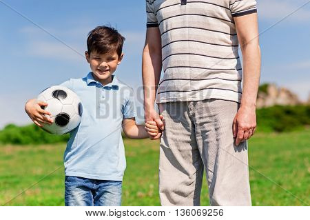Cheerful family came to play football in a park. The boy is holding a male hand and a ball. He is standing and smiling