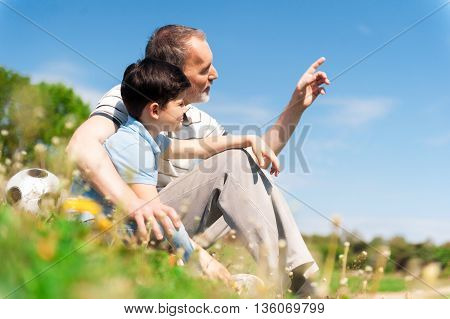 Mature grandfather is explaining something to his grandson. He is embracing the boy and pointing finger forward with concentration. They are sitting on grass near a ball