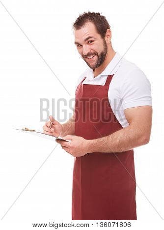 Handsome Smiling Man With Red Apron Writes On A Black Clipboard