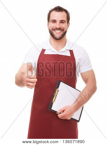Young Happy Man With Red Apron Makes A Gesture Thumb Up On White Background