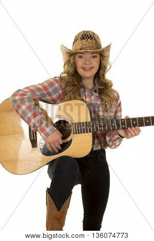 a woman with down syndrome with a smile in her western gear playing her guitar.