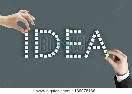 Hands arranging word idea with small cubes on dark grey background. Idea concept