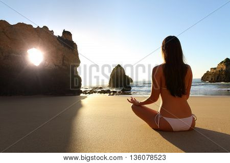 Back view of a full body of a girl wearing bikini doing yoga exercises in the beach at sunrise in front of the sun