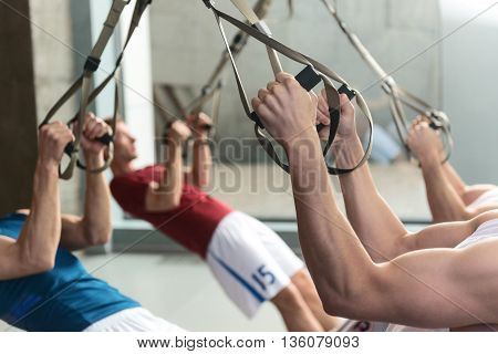 Fit young sportsmen exercising with trx equipment in group