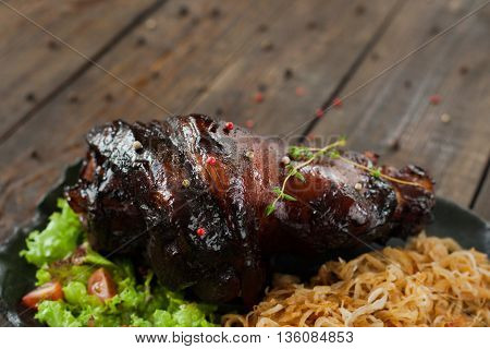 Baked pork leg with braised cabbage copyspace. Black plate with backed pork leg with braised cabbage, lettuce and tomatoes on wooden background. Free space and Junk food
