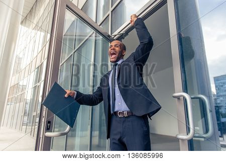 Low angle view of handsome young Afro American businessman in classic suit holding folder keeping fist up and screaming with happiness while leaving office building poster