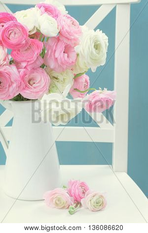 Pink and white ranunculus flowers in vase on chair with blue background, retro toned