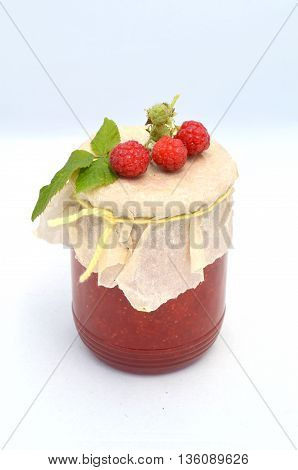 Bank of raspberry jam on a white background and fresh raspberries close
