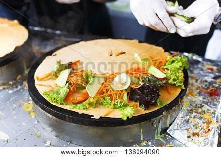 Making vegetable crepe at pan. Salty crepe or pancake with fillings made by street vendor's hands at outdoors creperie. French cuisine, cooking for commercial kitchen. poster