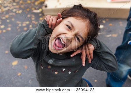 ZAGREB, CROATIA - OCTOBER 14, 2013: Portrait of cute Roma girl  posing for camera at garbage dump.