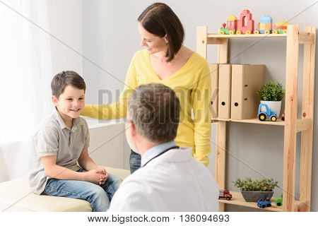 Doctor ready to make you well. Smiling young boy listening to pediatrician, sitting in doctors office