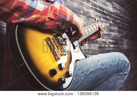 Side view of casual man playing electric sunburst guitar on wooden background. Closeup