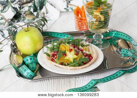 Dietary salad with orange, pomegranate and carom, centimeter for a good figure, a tray