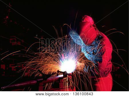 welder with sparks black background magenta blue