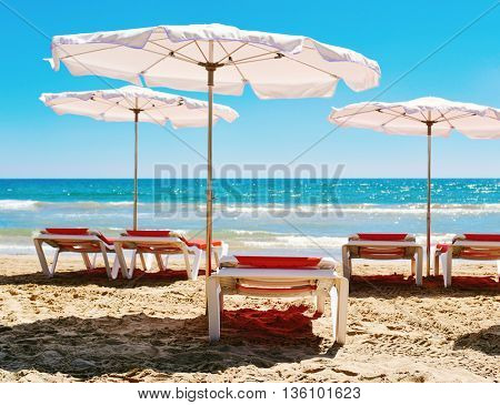 some colorful orange sunloungers and some white umbrellas in a quiet beach in the Mediterranean sea